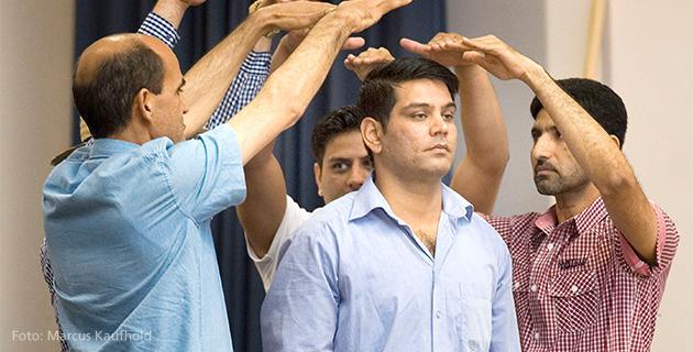 Männer stellen mit Armen Dach dar auf Theaterbühne