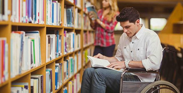 Student im Rollstuhl vor Bücherregal