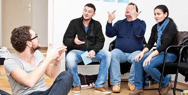 Vier Personen unterhalten sich in Gebärdensprache