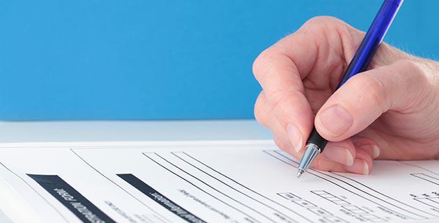 Detailbild einer Hand die ein Formular ausfüllt