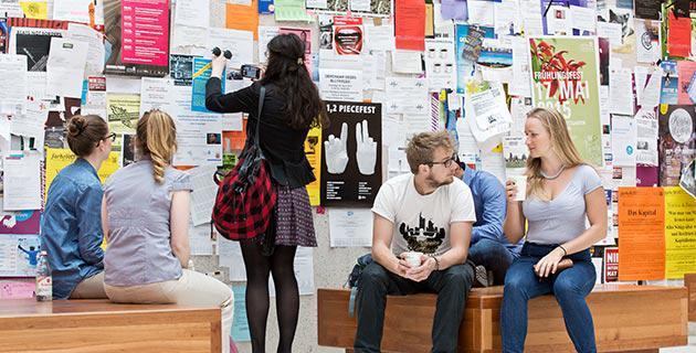 Studierende vor einem schwarzen Brett in der Uni