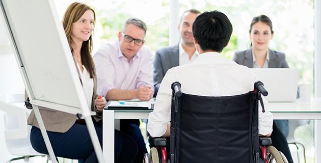 Personen in einer Meetingsituation, Mann im Rollstuhl und vier Kollegen und Kolleginnen
