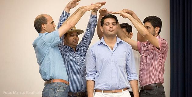 Männer stellen mit Armen Dach dar auf Theaterbühne 2