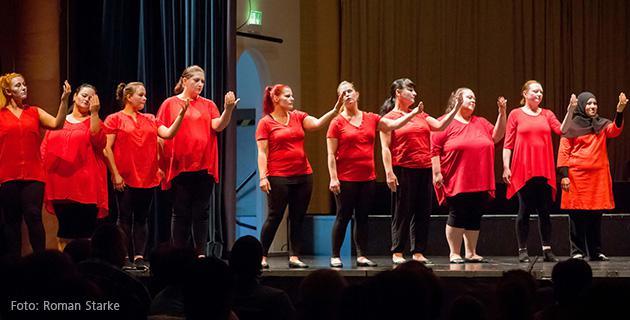 Bild einer Aufführung, Damen in roten Oberteilen
